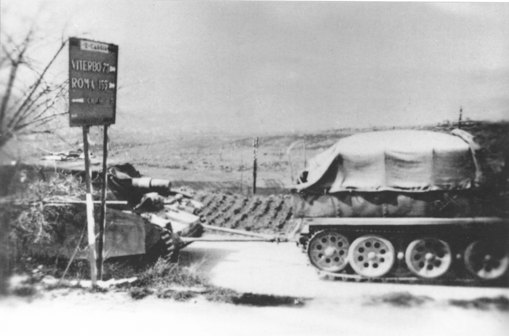A Sturmpanzer being towed by an Sd.Kfz. 9. Based on the road sign this spot is 155 km from Rome and 73 km from Viterbo which puts it about 50 km south of Sienna. This is the general area projected for the rest stop at the end of the third nights travel. One cant say for certain this photograph was taken during this particular road march but it may have been.